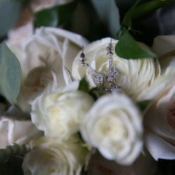 Strauss studios captures a detail shot of stunning bridal jewelry atop romantic white roses
