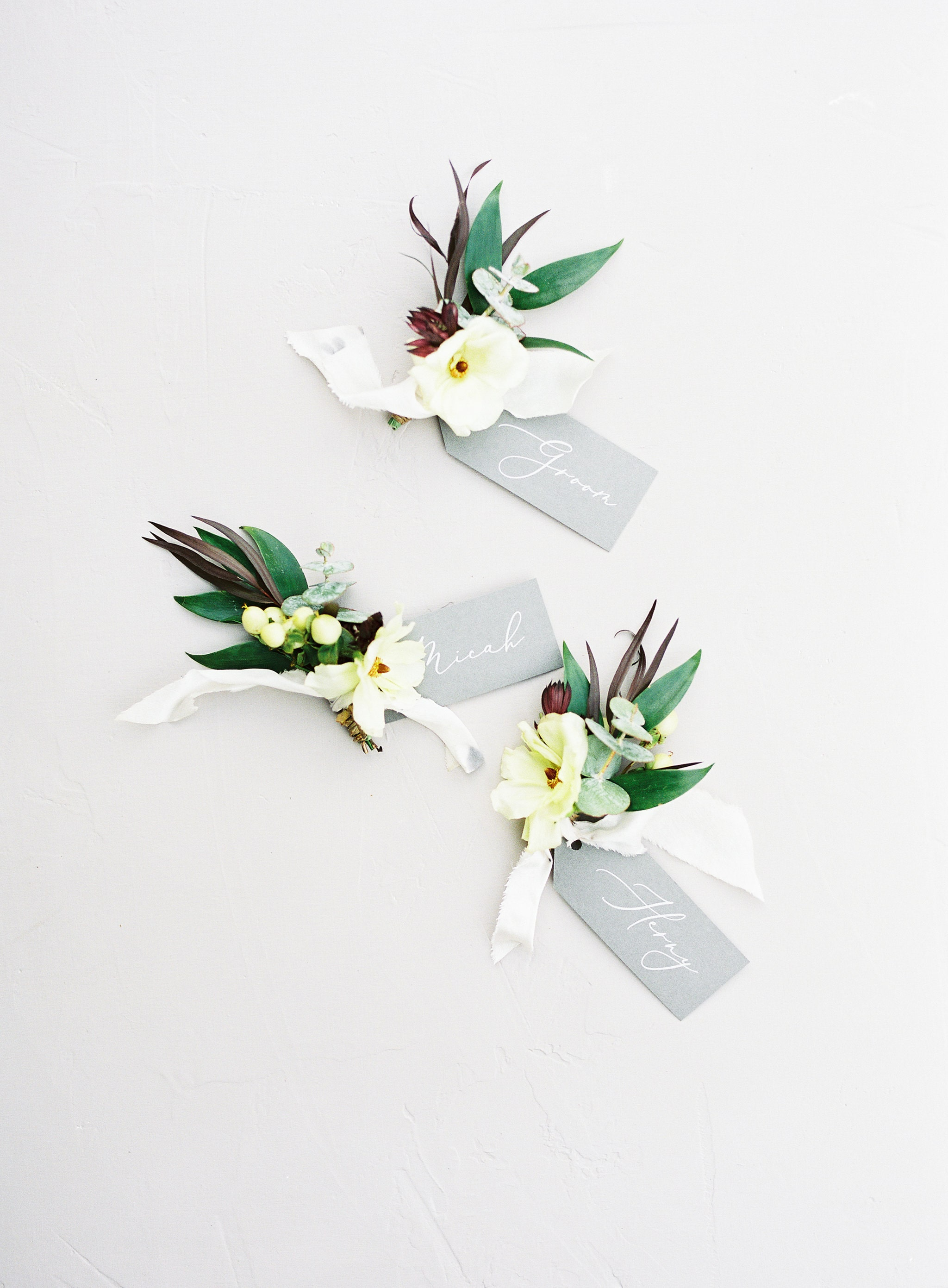 Groomsmen boutineers show off simple white flowers and varied green accents by Whats Up Buttercup and captured by Sunshower Photography