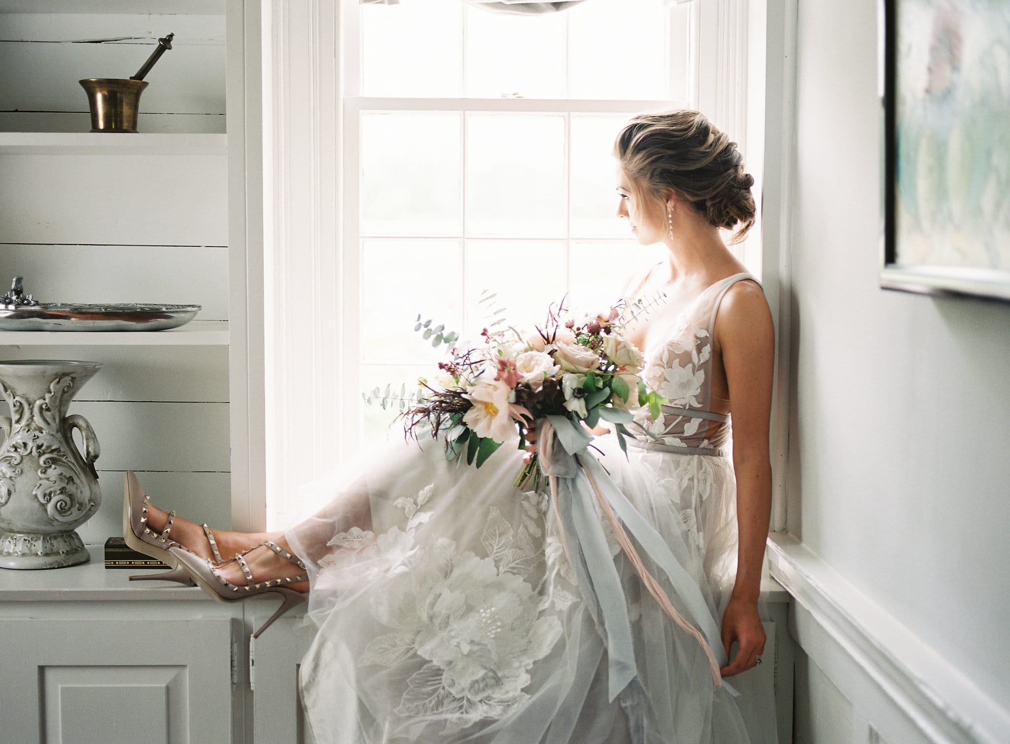 Bride relaxes at Tipsy Goat Estate in a stunning dress from Watters and stunning drop earrings BHLDN and a romantic bouquet created by Whats Up Buttercup
