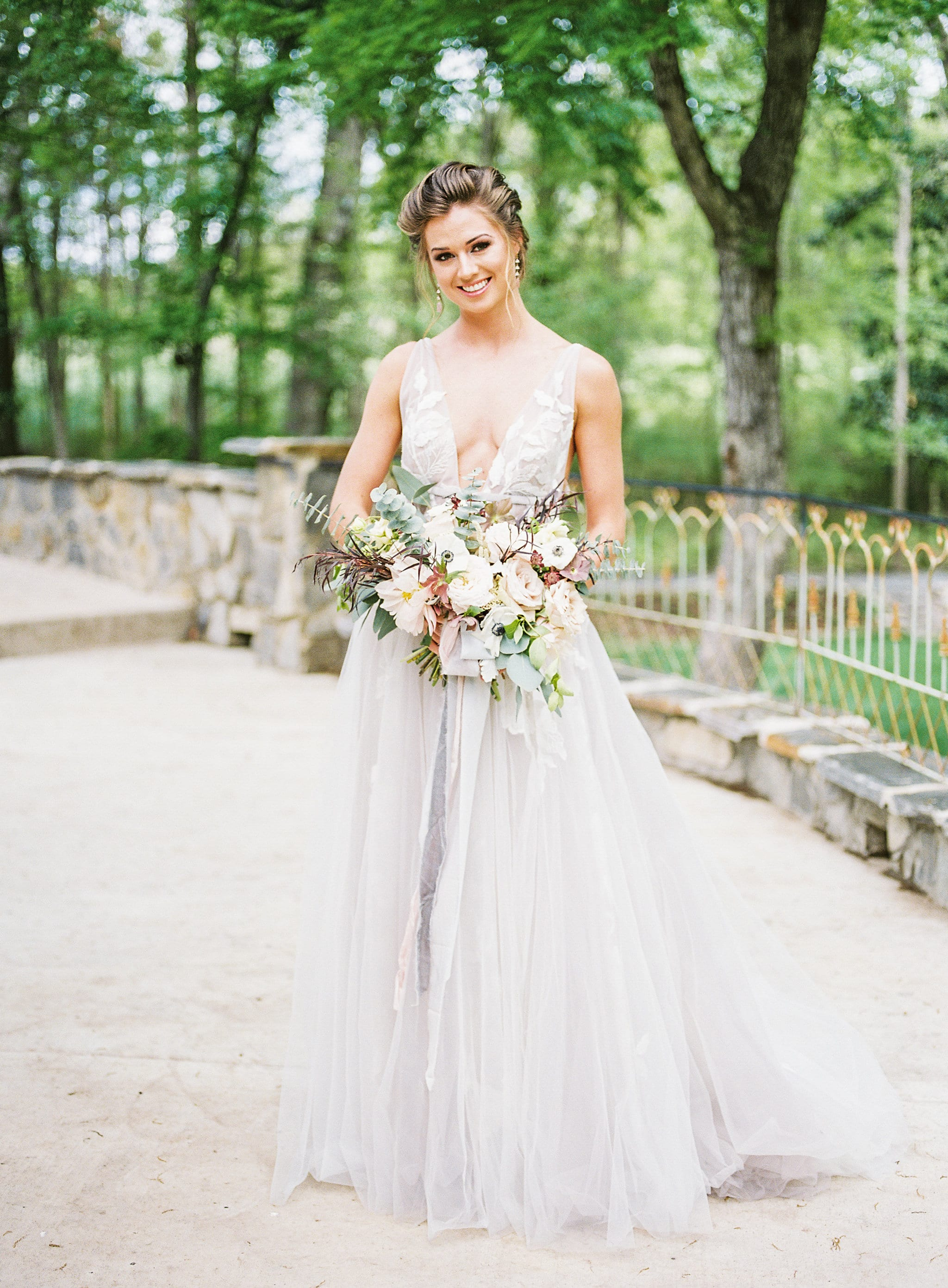 Bride poses with stunning bouquet created by Whats Up Buttercup for a styled shoot at Tipsy Goat Estate designed by Magnificent Moments Weddings