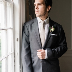 Groom poses at Tipsy Goat Estate wearing a suite by Alton Lane
