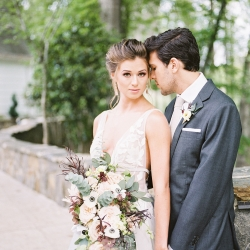 Bride wearing a Watters gown poses with her groom wearing an Alton Lane suite and holding a stunning bouquet by Whats Up Buttercup