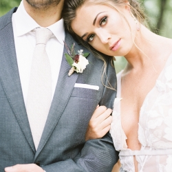 Bride poses in a dress by Watters with her groom wearing a suit by Alton Lane during a styled shoot at Tipsy Goat Estate designed by Magnificent Moments Weddings