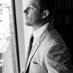 Groom puts on his suite as he prepares for his wedding at the Kimpton Tryon Park before his fall wedding captured by Sunshower Photography