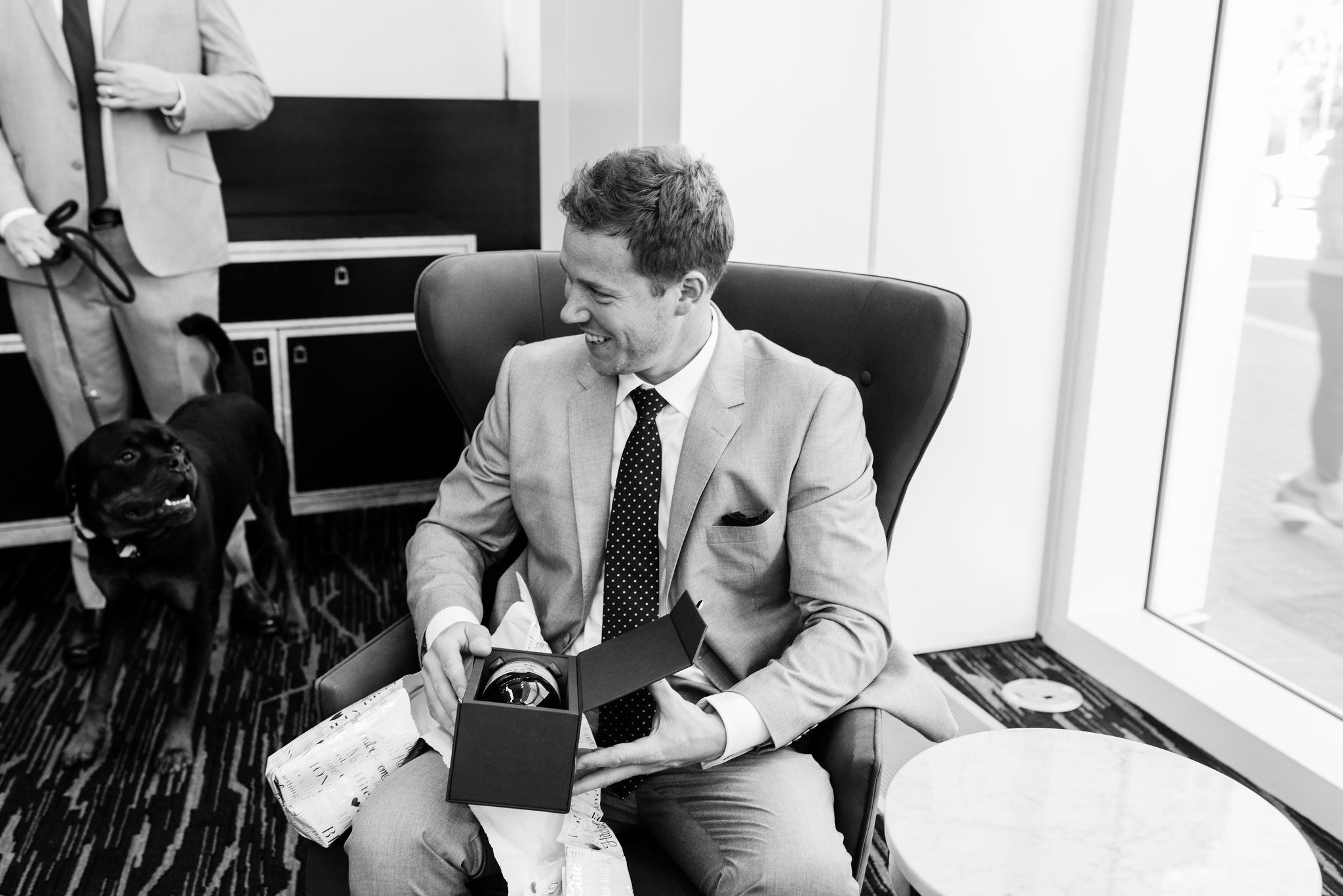 Groom opens a gift as he prepares for his wedding at the Kimpton Tryon Park captured by Sunshower Photography