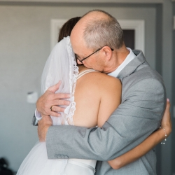 Sunshower Photography captures a sweet moment between a bride and her father after he sees her in her gown before her wedding at Triple C Barrel Room