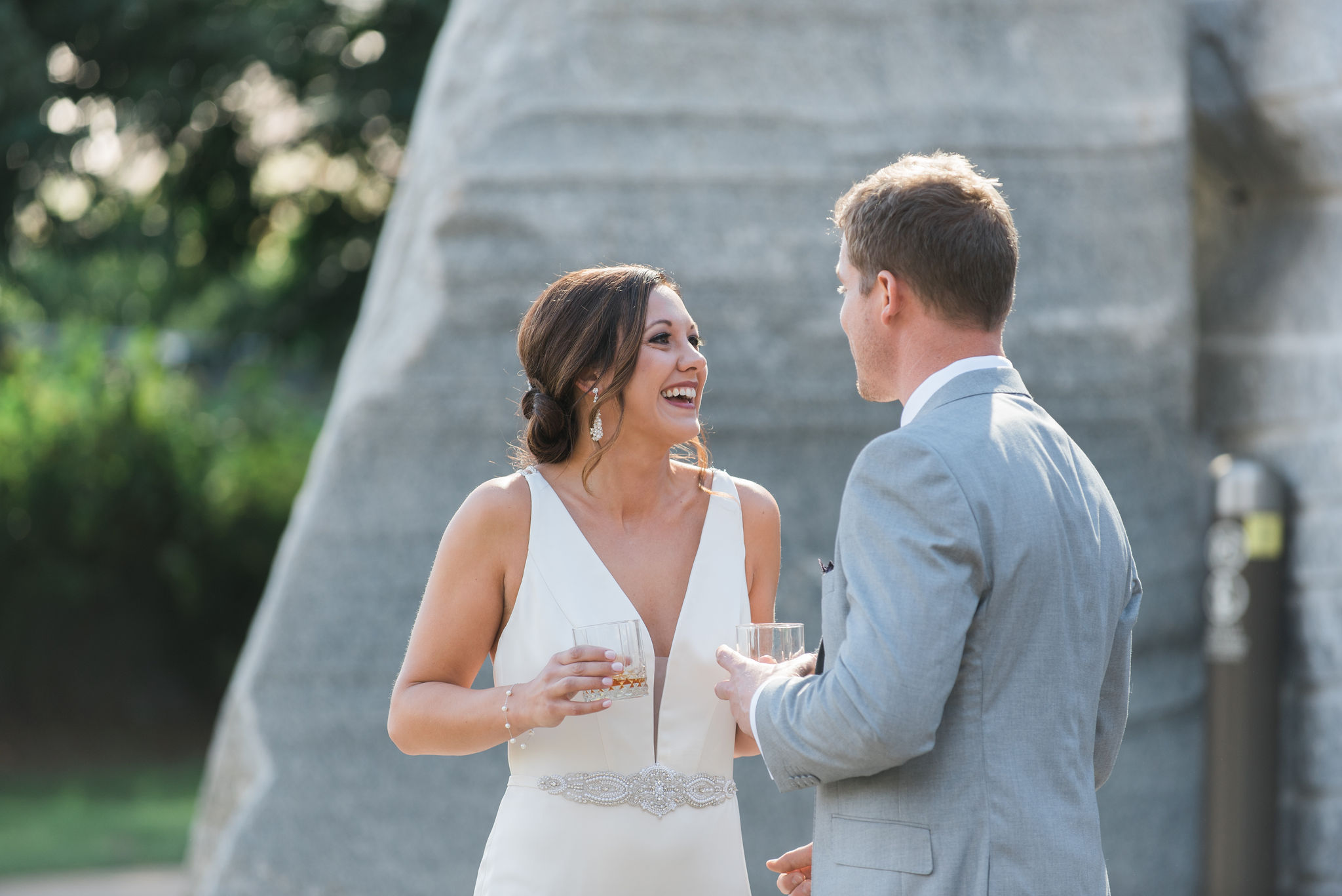 Bride has stunning makeup by Simply Beautiful Artistry and wears a plunging neckline dress from Poffie Girls