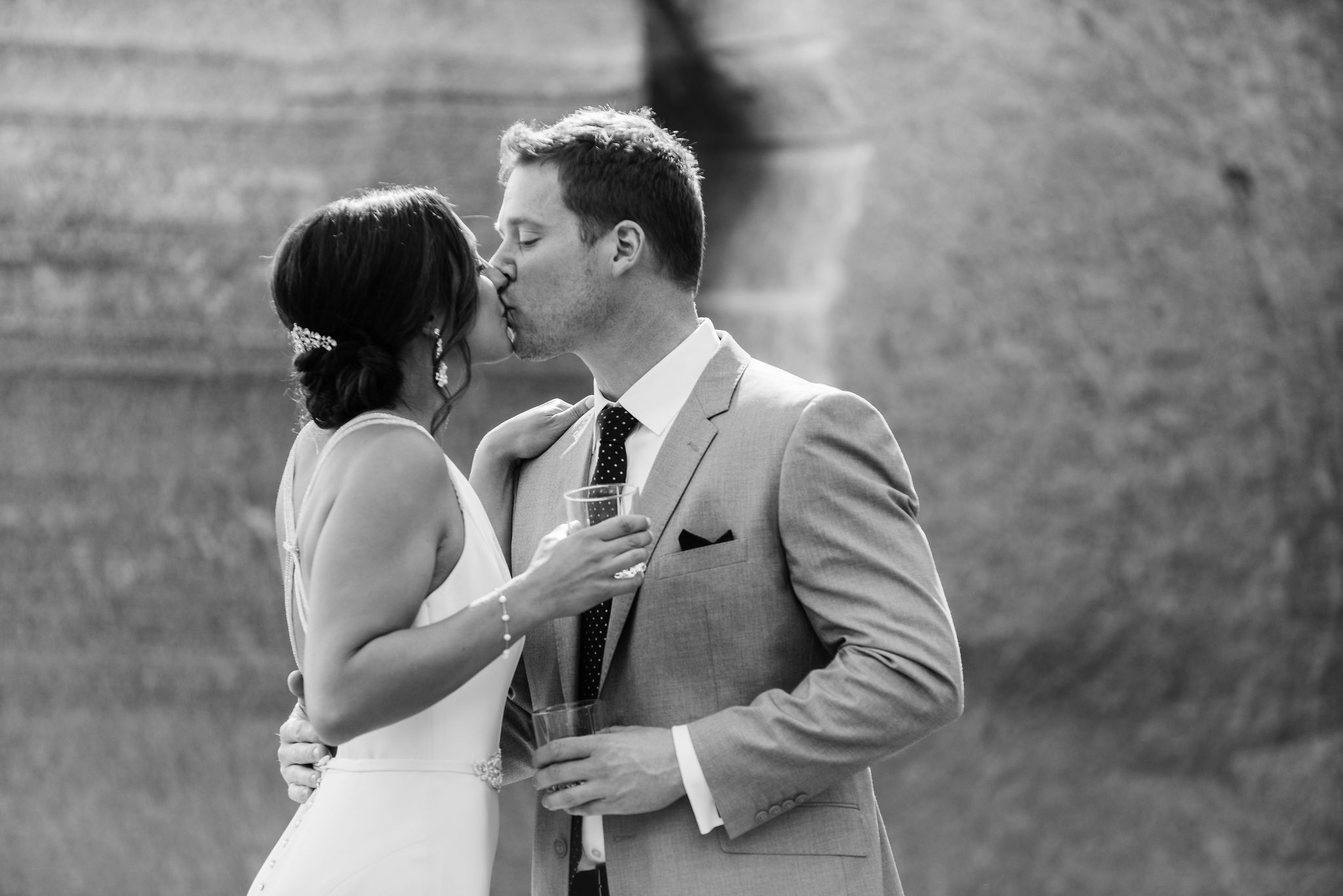 Bride and groom share a kiss before their fall wedding, the bride has a low updo accent by a jewel barrette a loot that was created by Simply Beautiful Artistry