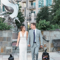 Bride and groom pose with their pet dogs in Uptown Charlotte during their fall wedding at Triple C Barrel Room