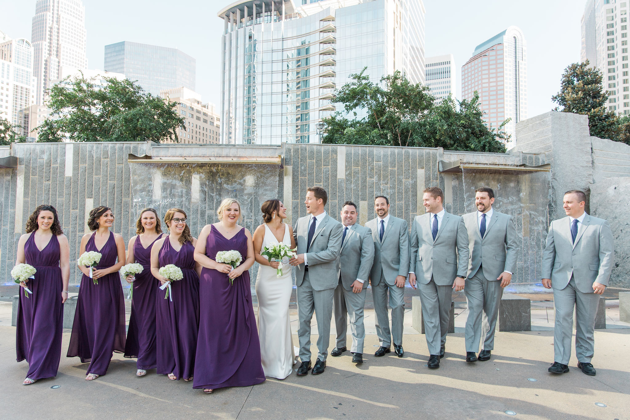 Bride and groom pose with bridal party in Uptown Charlotte, bridesmaids wearing deep purple dresses and groomsmen in cool gray suites all captured by Sunshower Photography