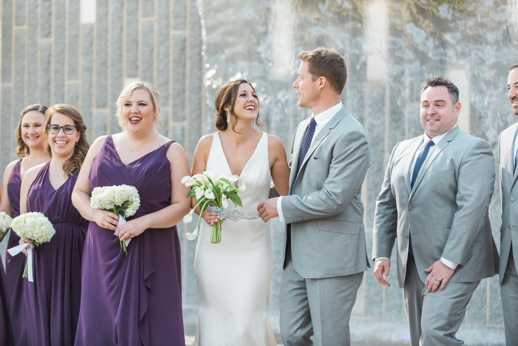 Bride and groom share a fun pose with their bridal party in Uptown Charlotte captured by Sunshower Photography