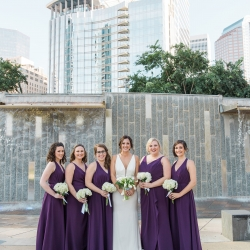 Bride poses with her bridesmaids who wear deep colored dresses and hold stunning white bouquets created by Carolyn Shepard Design