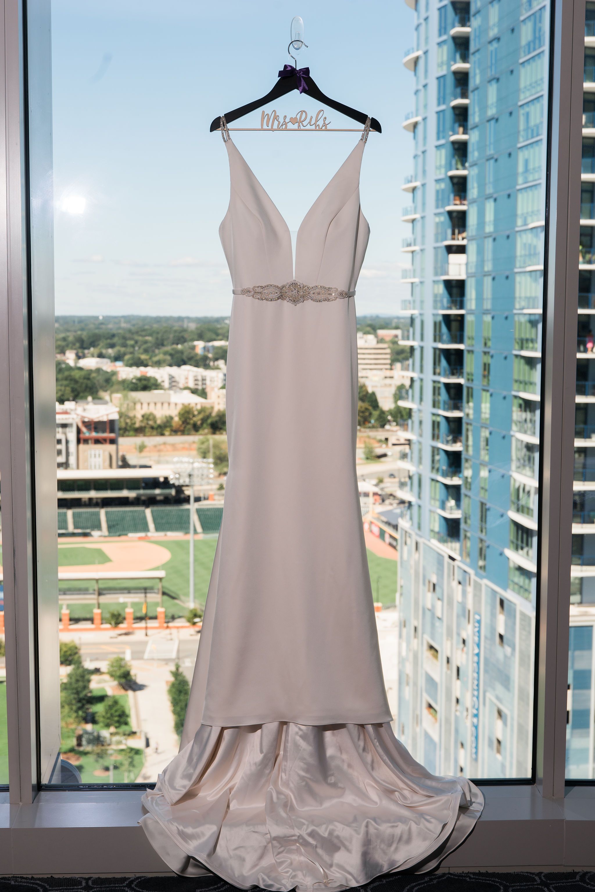 The Kimpton Tryon Park creates a great cityscape background for a stunning shot of a Poffie Girls gown by Sunshower Photography