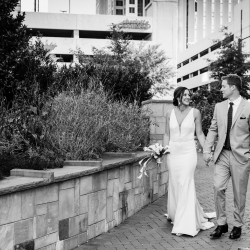 Bride and groom walk in Uptown Charlotte after their ceremony at Triple C Barrel Room captured by Sunshower Photography