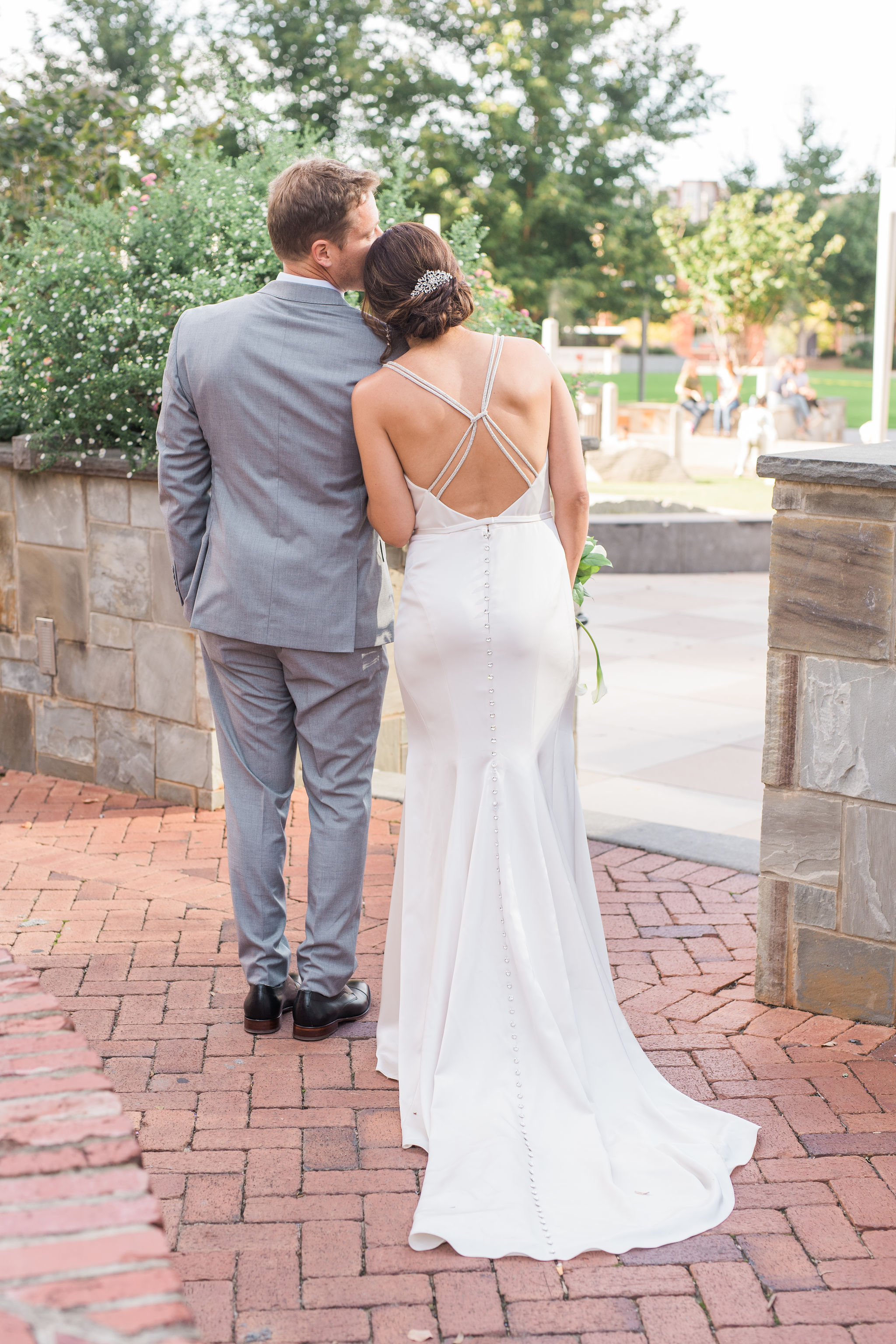 Bride wears a stunning dress by Poffie Girls with jeweled straps and walks with her groom during their fall wedding at Triple C Barrel Room