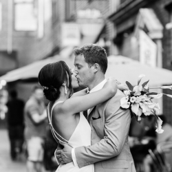 Bride and groom kiss in a city setting after their fall wedding at Triple C Barrel Room coordinated by Magnificent Moments Weddings
