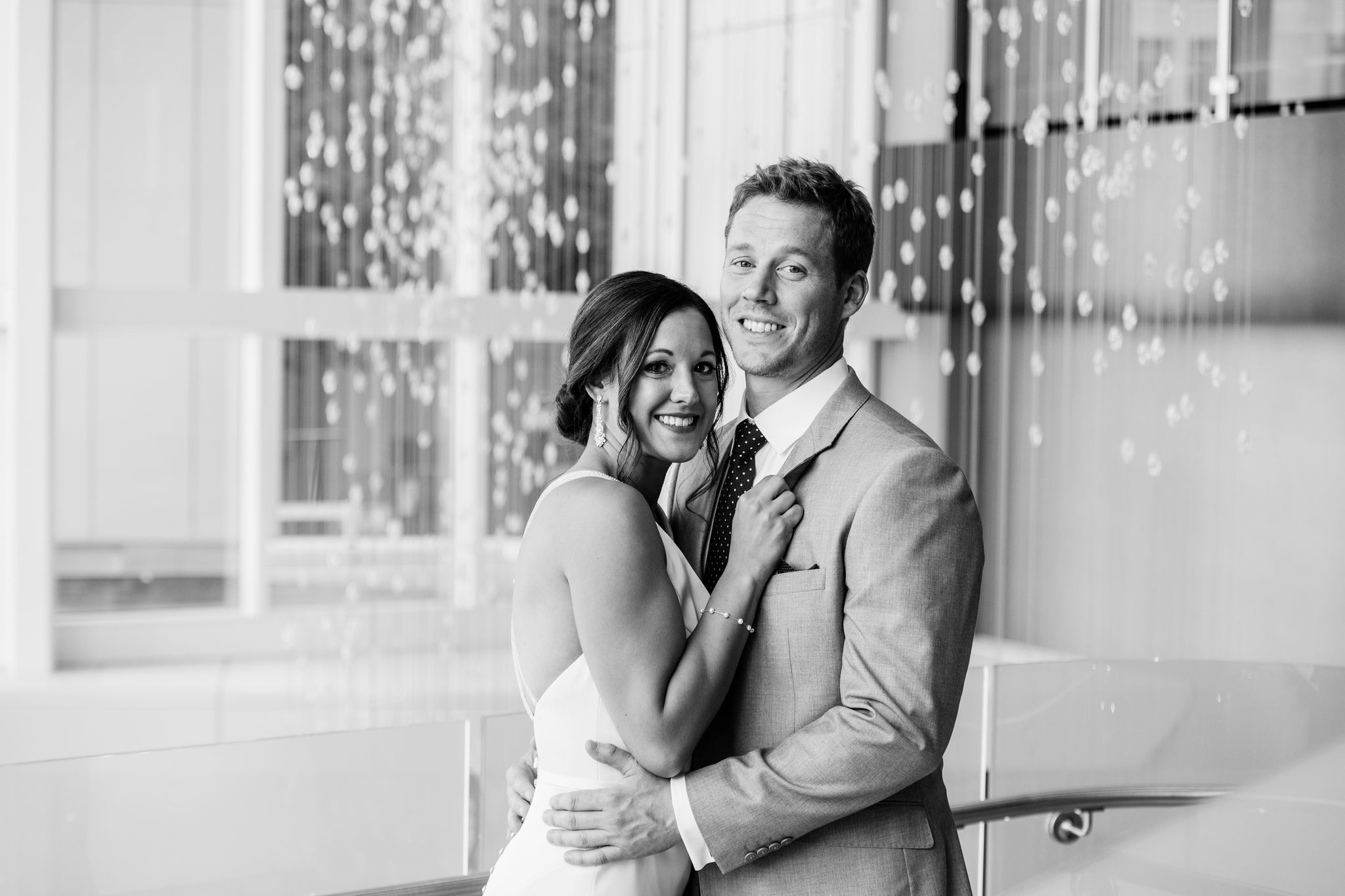 Bride and groom pose among hanging lights during their fall wedding captured by Sunshower Photography