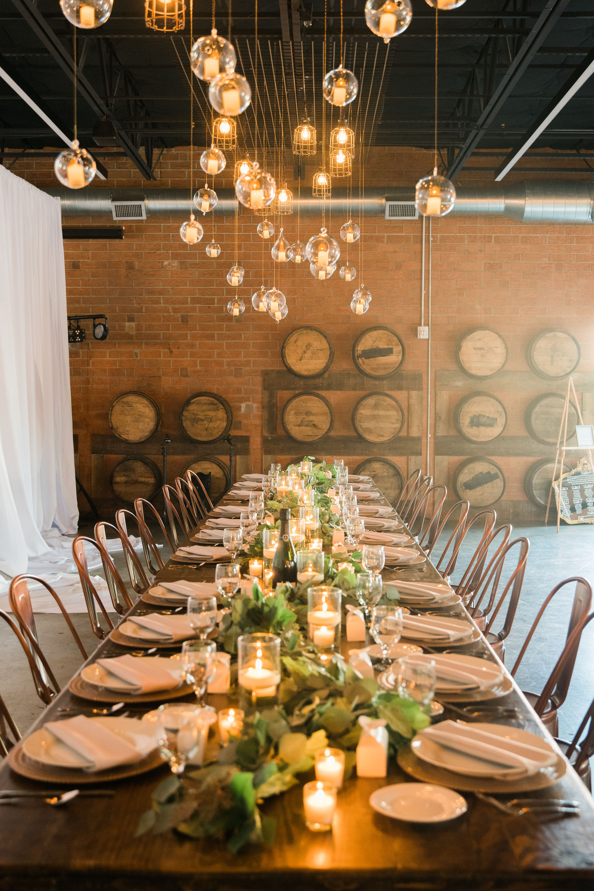 A stunning long table accent by a long greenery garland created by Carolyn Shepard Design for a fall wedding at Triple C Barrel Room