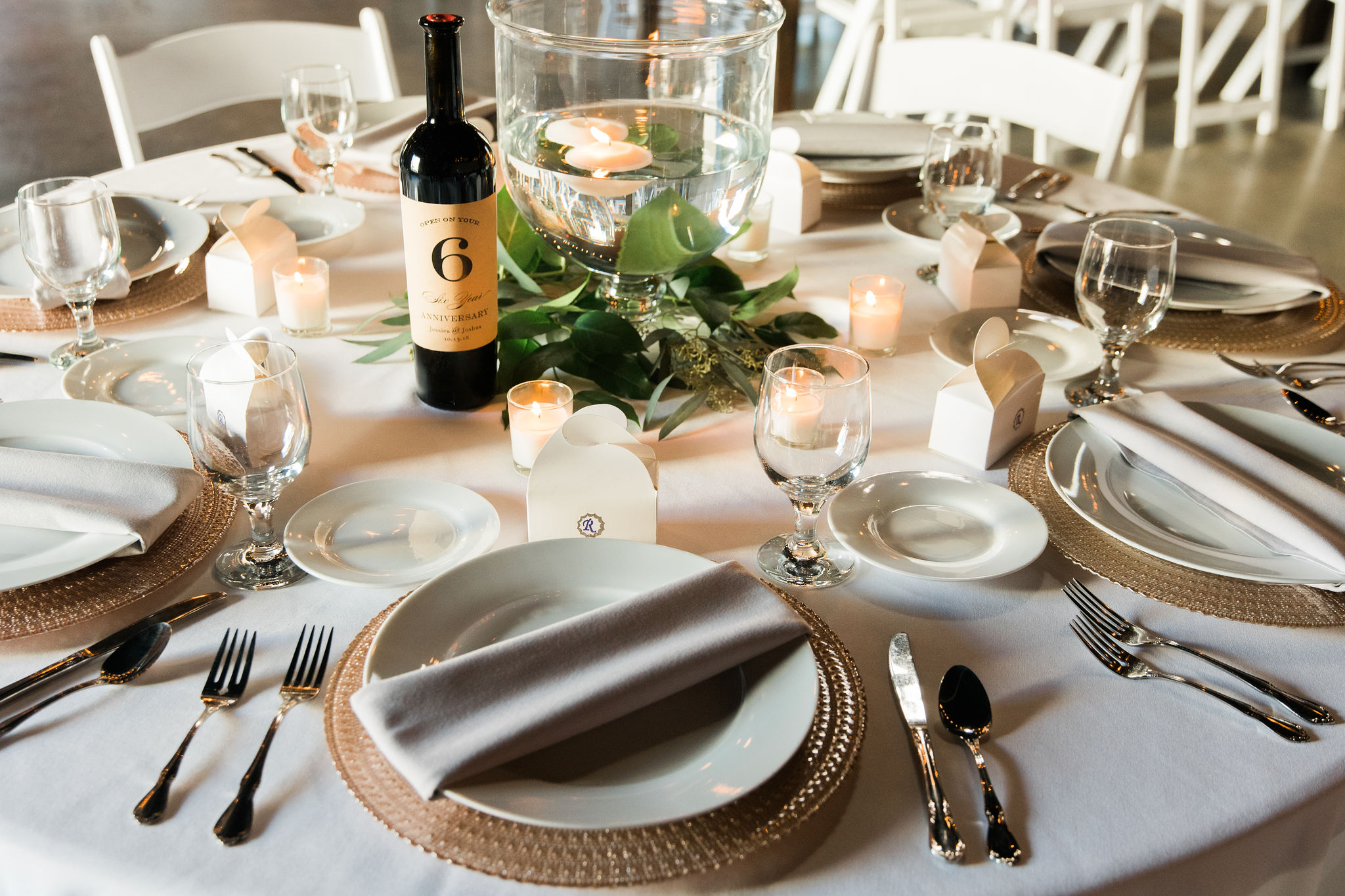 Neutral table setting features ivory napkins, simple white plates, and gold charges. all centered around a glass vase with delicate floating candles all for a fall wedding at Triple C Barrel Room