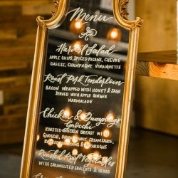 Best Impressions Catering created a great menu for a fall wedding at Triple C Barrel Room which appears on a gold antique mirror captured by Sunshower Photography