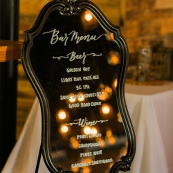 Antique mirror serves as a bar menu for a fall wedding at Triple C Barrel Room captured by Sunshower Photography