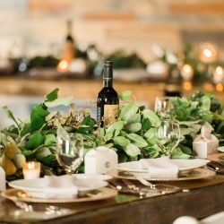 Carolyn Shepard Designs provided stunning greenery garlands accented by by simple white plates and detailed gold chargers at a fall wedding at Triple C Barrel Room