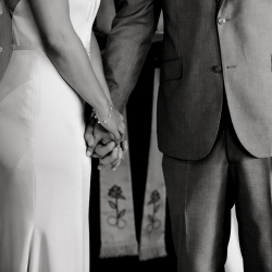 Detail shot of bride and groom holding hands as they exchange vows during their ceremony at Triple C Barrel Room coordinated by Magnificent Moments Weddings