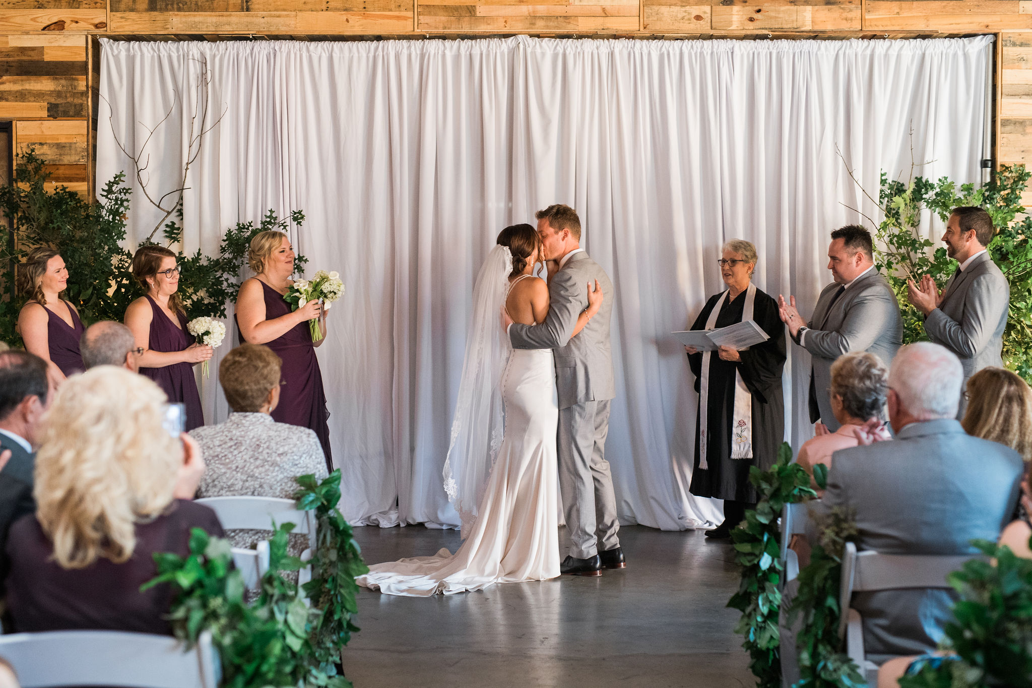 Bride and groom exchange a kiss after their vows at Triple C Barrel Room captured by Sunshower Photography