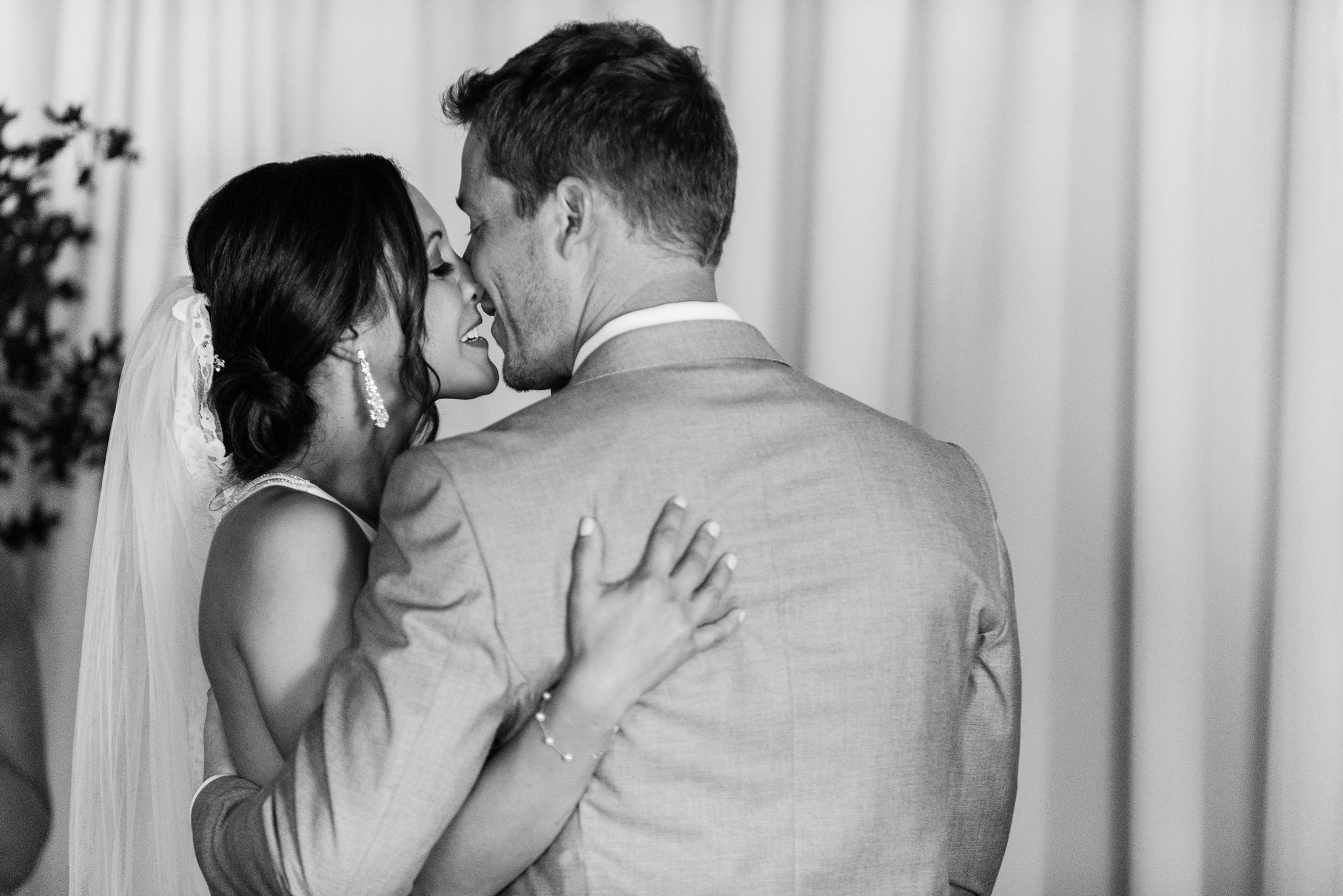 Bride and groom kiss after a wedding ceremony coordinated by Magnificent Moments Weddings