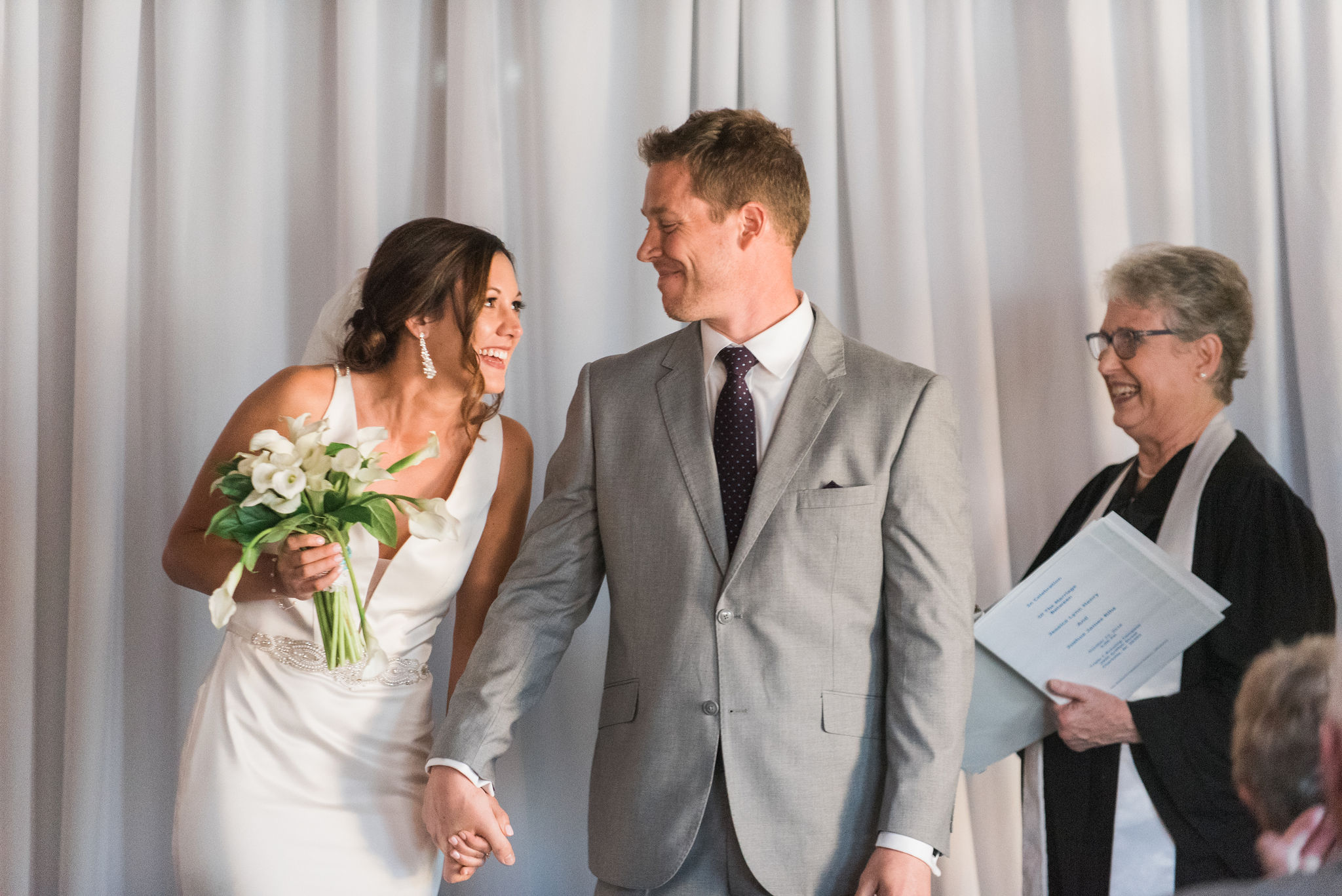 Bride and groom exchange a smile after being married during a fall weeding ceremony captured by Sunshower Photography