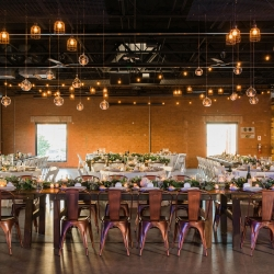 Vintage metal charges combine with hanging lights and accented greenery during a fall wedding at Triple C Barrel Room captured by Sunshower Photography