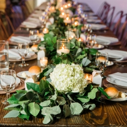 Simple greenery garland is accented with white hydrangeas and elegant floating candles for a fall wedding at Triple C Barrel Room during a fall wedding coordinated by Magnificent Moments Weddings