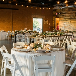 Simple white linens and chairs make a subtle impact against the brick walls and edison lights of the reception space at Triple C Barrel Room