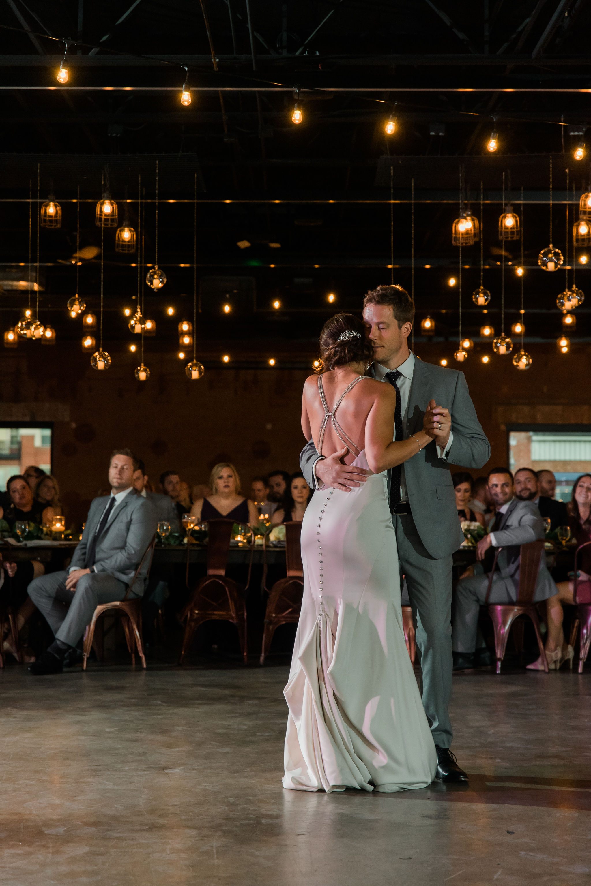 Sunshower Photography captures a bride and groom sharing their first dance during their wedding reception at Triple C Barrel Room