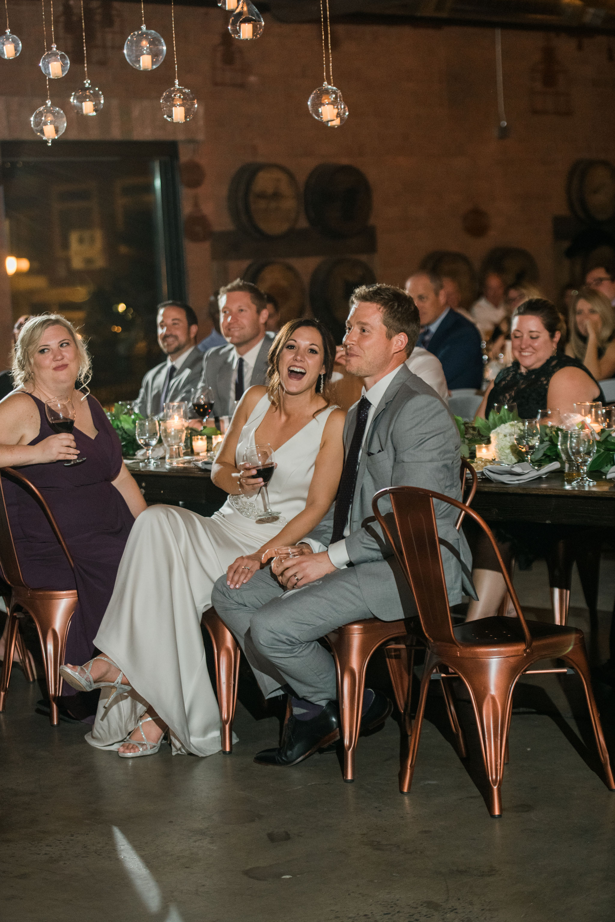 Bride and groom enjoy toasts from friends and family during their fall reception coordinated by Magnificent Moments Weddings