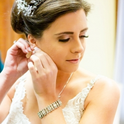 Taylor Main Photography captures a bride putting on her jewelry as she prepares for her Uptown Charlotte wedding