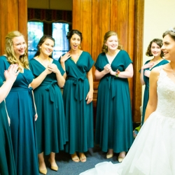 Bridesmaids react to a brides stunning dress before she walks down the aisle at St Peter's Catholic Church