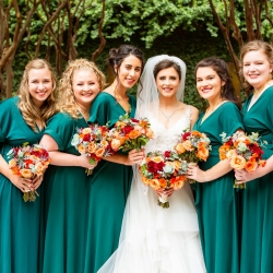 Taylor Main Photography capture a bride and her bridesmaids wearing deep green dresses and holding fall floral bouquets created by Magnificent Moments Weddings