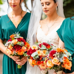 Bride poses with her bridesmaids holding stunning fall bouquets created by Magnificent Moments Weddings