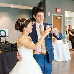 Bride and groom share a toast with their family and friends during their wedding reception coordinated by Magnificent Moments Weddings