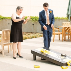Wedding guests enjoy cornhole during a daytime wedding at The Westin in Uptown Charlotte