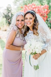 Bride poses with her mother for her spring wedding coordinated by Magnificent Moments Weddings
