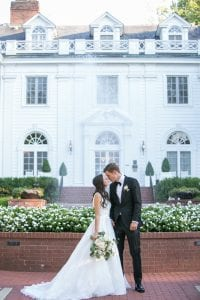 Bride and groom pose in front of the historic Duke Mansion during their summer wedding coordinated by Magnificent Moments Weddings