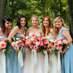 Bride poses with bridesmaids wearing soft blue dresses and holding amazing pink bouquets designed by Nkemdi Thompson for a Fort Mill South Carolina wedding at The Diary Barn
