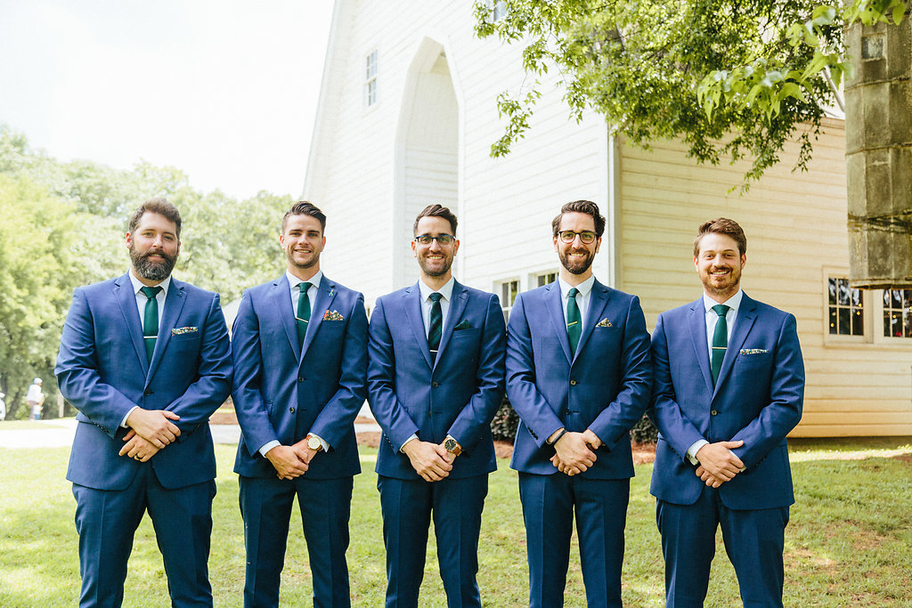 Groom and groomsmen stand in front of the Dairy Barn before their spring wedding captured by Alivia Photography