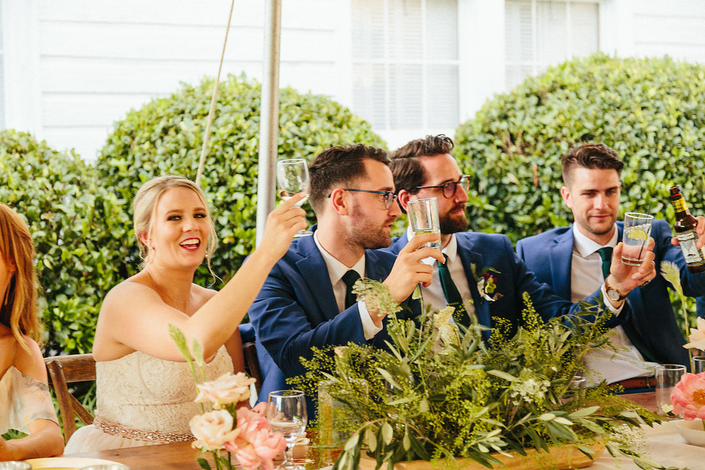 Bride and groom raise a glass in toast with their bridal party during their wedding reception at The Diary Barn captured by Alivia Photography