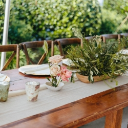 Farmhouse tables rented from creative solutions are the prefect setting of organic greenery centerpieces created by Nkemdi Thompson for a spring Dairy Barn Wedding