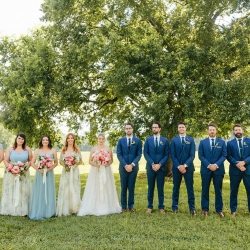 Bride and groom pose with bridal party beneath a tree at The Diary Barn during their spring wedding captured by Alivia Photography