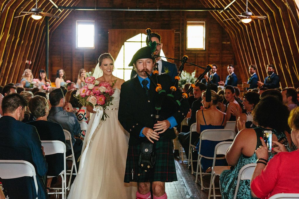 Bride and groom trail behind a piper after their wedding ceremony at The Diary Barn coordinated by Magnificent Moments Weddings