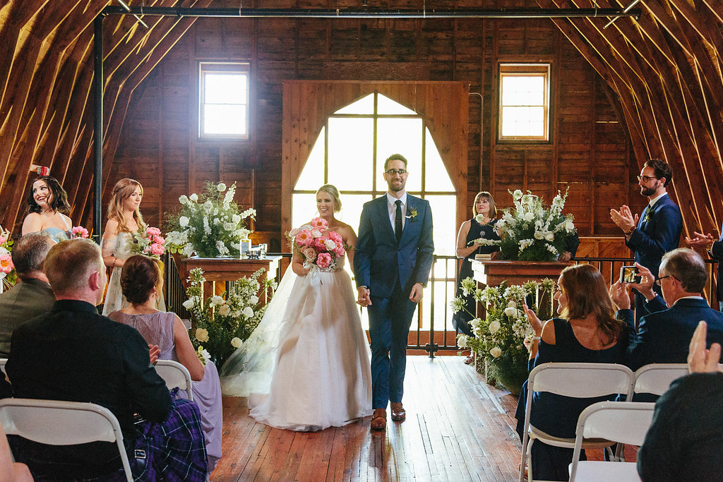 Bride and groom exit their ceremony coordinated by Magnificent Moments Weddings at The Diary Barn in Fort Mill South Carolina